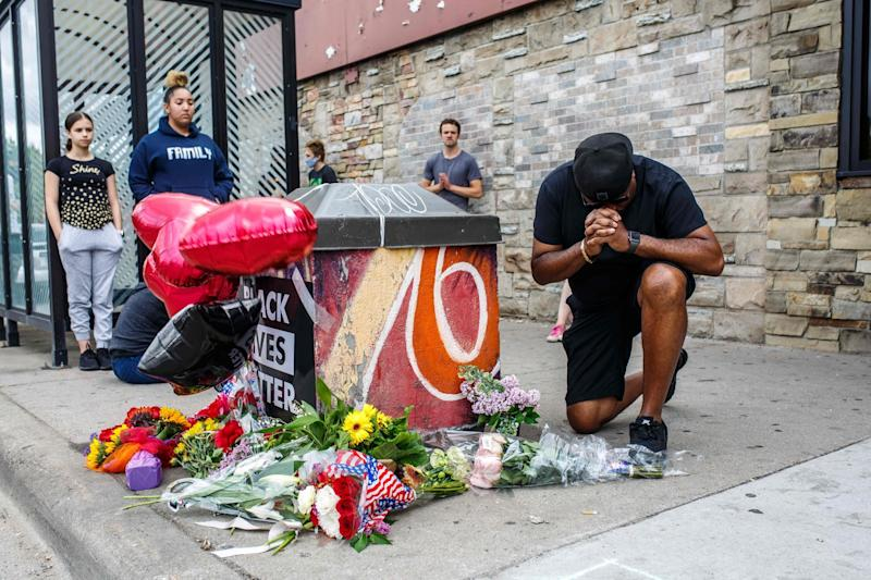 A protester prays in front of George Floyd's memorial in Minneapolis: AFP via Getty Images