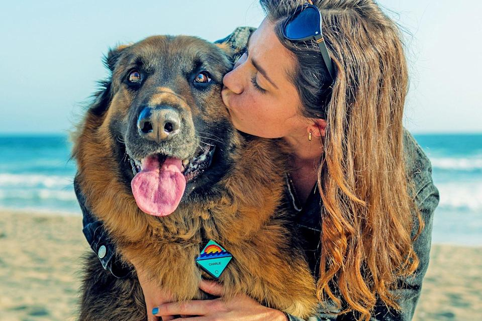 woman kissing dog that is wearing his QALO tag