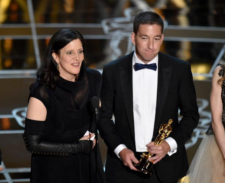 """Laura Poitras, left, and Glenn Greenwald accept the award for best documentary feature for """"Citizenfour"""" at the Oscars on Sunday, Feb. 22, 2015, at the Dolby Theatre in Los Angeles. (Photo: John Shearer/Invision/AP)"""