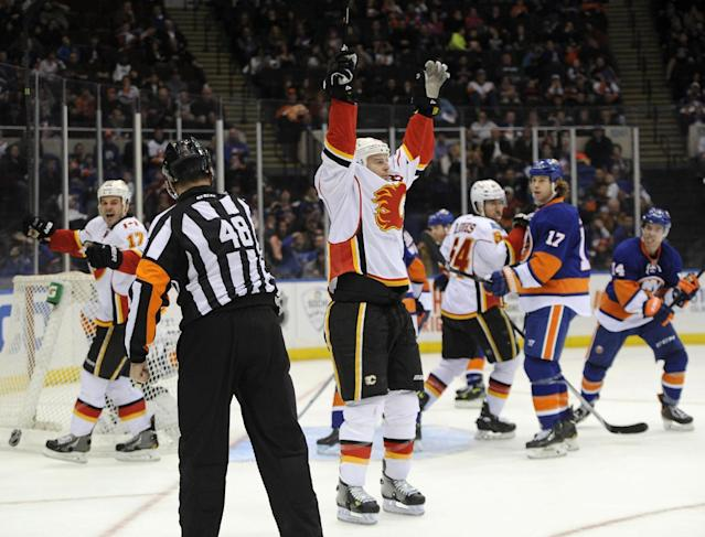 Calgary Flames' Matt Stajan (18), center, and Lance Bouma (17) celebrate Stajan's goal as New York Islanders' Matt Martin (17) and Thomas Hickey (14) react in the third period of an NHL hockey game, Thursday, Feb. 6, 2014, in Uniondale, N.Y. The Flames won 4-2. (AP Photo/Kathy Kmonicek)