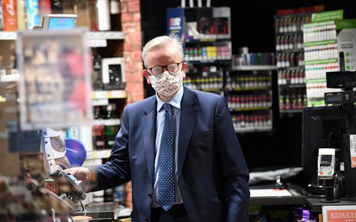 Chancellor of the Duchy of Lancaster Michael Gove making a purchase in a shop near St James's Park in Westminster, London. Wearing face masks in shops will become mandatory in England from July 24 - Stefan Rousseau