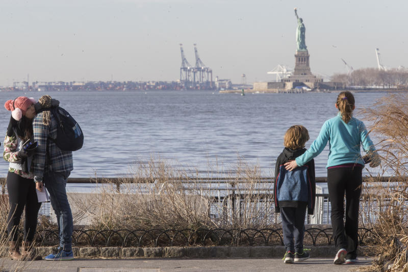 "Visitors to the Statue of Liberty take in the sight from battery park, Saturday, Jan. 20, 2018, in New York. The National Park Service announced that the Statue of Liberty and Ellis Island would be closed Saturday ""due to a lapse in appropriations."" Late Friday, the Senate failed to approve legislation to keep the government from shutting down after the midnight deadline. (AP Photo/Mary Altaffer)"