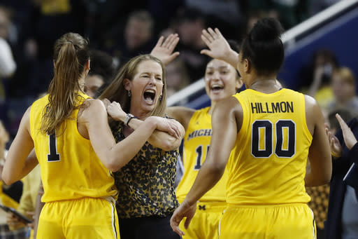 """FILE - Michigan head coach Kim Barnes Arico, second from left, celebrates the team's win over Michigan State with guard Amy Dilk (1) and forward Naz Hillmon (00) during the second half of an NCAA college basketball game in Ann Arbor, Mich., in this Sunday, Jan. 5, 2020, file photo. The Wolverines will be counting on Naz Hillmon, a 6-foot-2 junior who last season led the team with 17.4 points and 8.7 rebounds per game. One of the most important things with any program is experience, and having Naz back is tremendous,"""" Barnes Arico said. (AP Photo/Carlos Osorio, File)"""