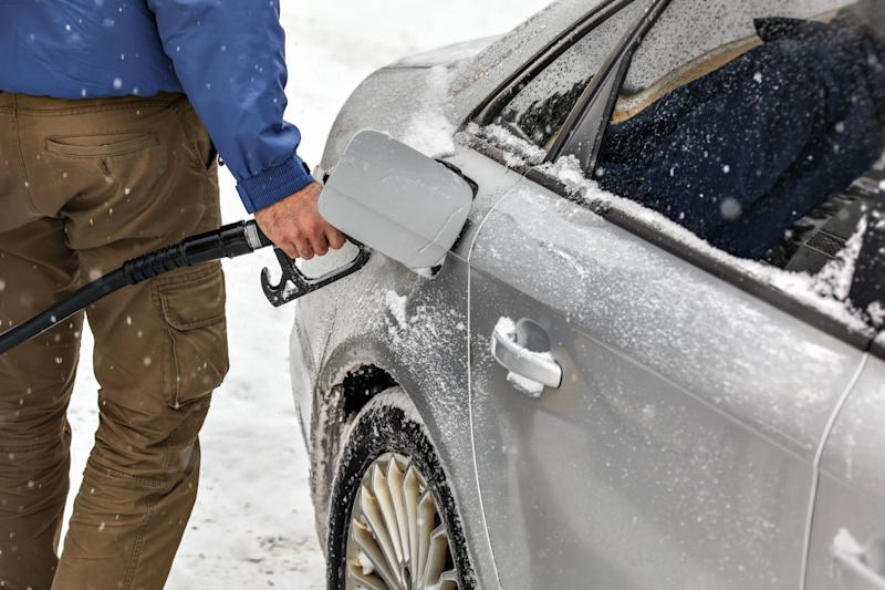 Man holding fuel nozzle, filling gas tank of car covered with snow in winter