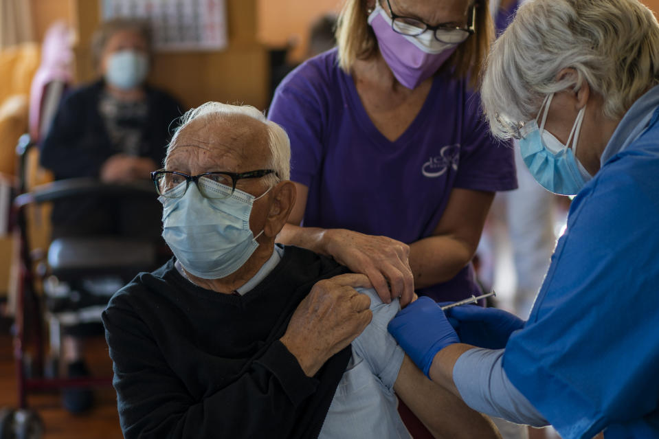 A nurse administers the Pfizer-BioNTech COVID-19 vaccine to a resident at Icaria nursing home in Barcelona, Spain, Tuesday, Jan. 12, 2021. Spain's rate of infection has shot up to 435 cases per 100,000 residents in the past two weeks, prompting new restrictions as authorities try to bring vaccination up to speed. (AP Photo/Emilio Morenatti)