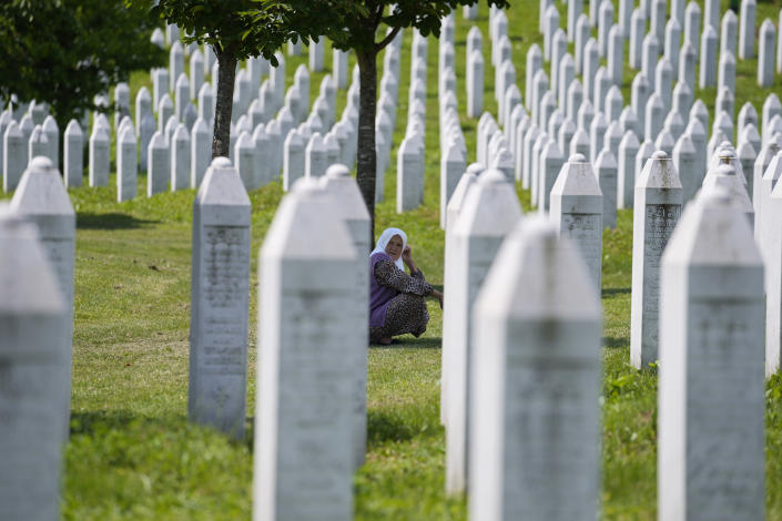 A woman crouches among the graves of victims of the Srebrenica massacre, at the memorial cemetery in Potocari, near Srebrenica, eastern Bosnia, Tuesday, June 8, 2021. Tuesday the United Nations court in The Hague, Netherlands, delivers its verdict in the appeal by former Bosnian Serb military chief Ratko Mladic against his convictions for genocide and other crimes and his life sentence for masterminding atrocities throughout the Bosnian war. (AP Photo/Darko Bandic)