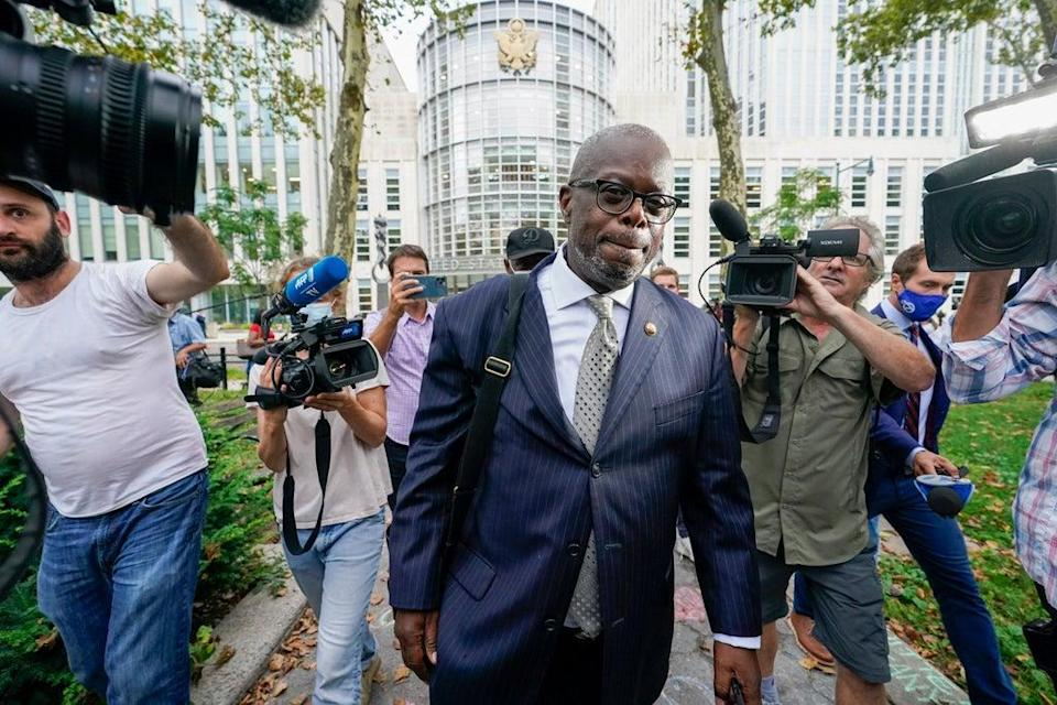 R Kelly's attorney Deveraux Cannick  is surrounded by reporters as he leaves Brooklyn Federal court (AP)