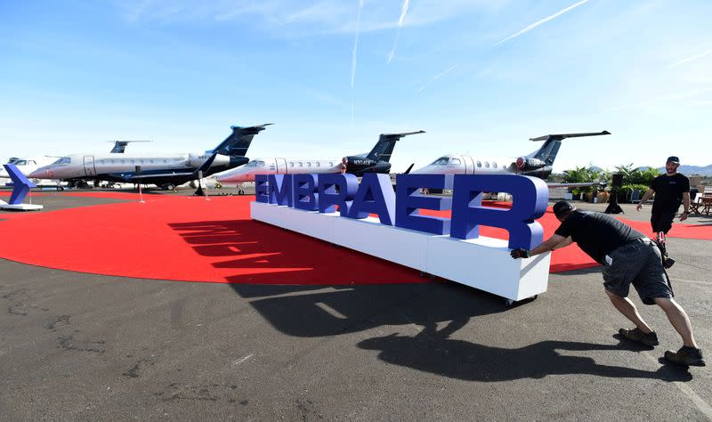 Workers set up at the Embraer booth prior to the opening of the National Business Aviation Association (NBAA) exhibition in Las Vegas