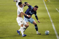 Vancouver Whitecaps's Jake Nerwinski, right, works against Los Angeles Galaxy's Cristian Pavon during the first half of an MLS soccer match, Sunday, Oct. 18, 2020, in Carson, Calif. (AP Photo/Marcio Jose Sanchez)