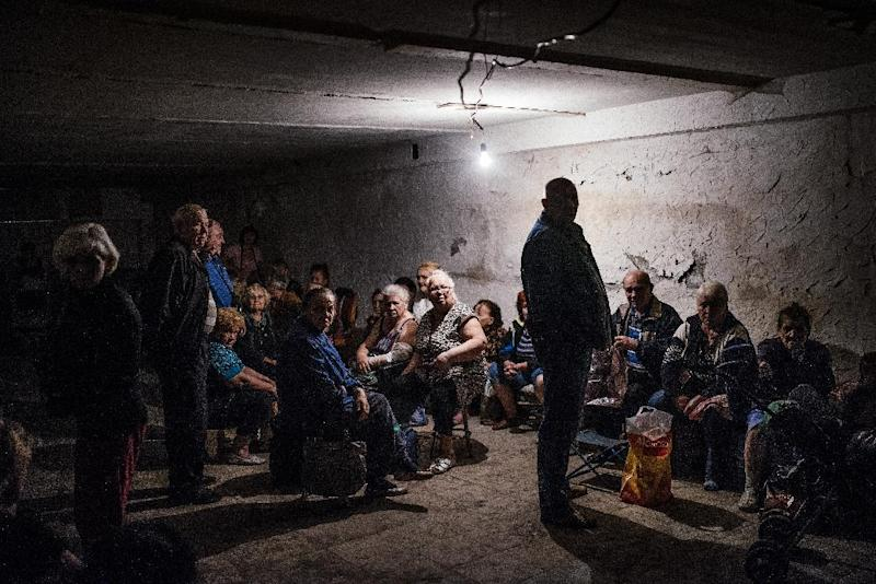 People sit inside a makeshift bomb shelter in the town of Makiyivka on August 19, 2014