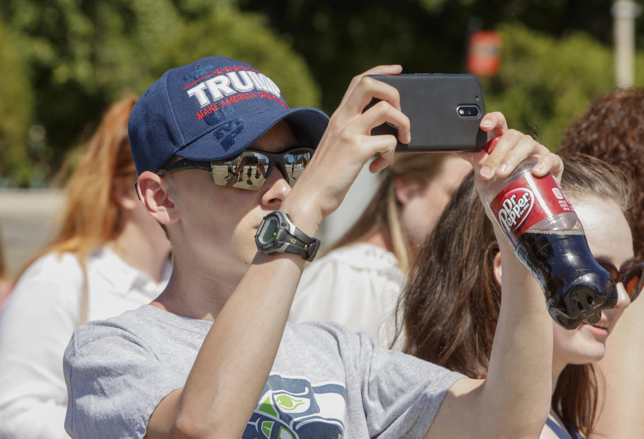 Bryce Howard, 15, of Everett, Wash., wears a Trump hat as he snaps a photo during a visit to the Supreme Court in Washington, Monday, June 26, 2017, where justices issued their final rulings for the term. The high court is letting a limited version of the Trump administration ban on travel from six mostly Muslim countries take effect, a victory for President Donald Trump in the biggest legal controversy of his young presidency. (AP Photo/J. Scott Applewhite)