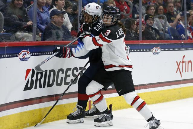 Canada's Jocelyne Larocque (3) checks United States' Alex Carpenter (25) during the first period of a rivalry series women's hockey game in Hartford, Conn., Saturday, Dec. 14, 2019. (AP Photo/Michael Dwyer)