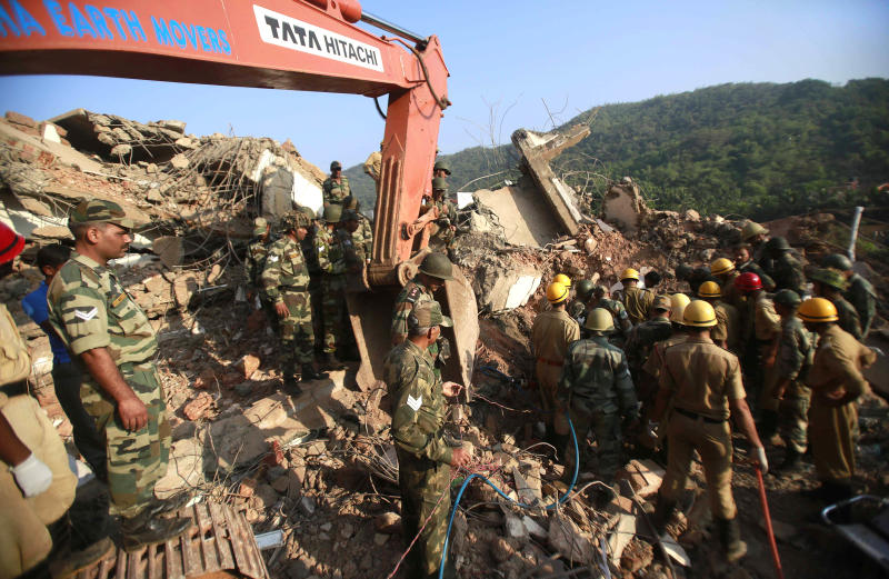 Indian army soldiers and fire officials look for survivors from the debris of a building that collapsed in Canacona, about 70 kilometers (44 miles) from Goa state capital Panaji, India, Sunday, Jan. 5, 2014. The five-story building under construction in the southern Indian state of Goa collapsed on Saturday, killing at least a dozen people and leaving dozens more feared trapped under the rubble, police said. (AP Photo/Rafiq Maqbool)