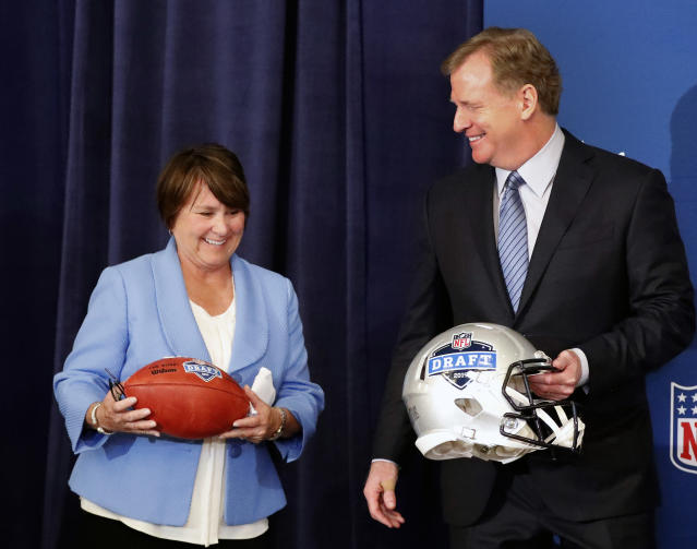 Tennessee Titans owner Amy Adams Strunk holds a football as she and NFL commissioner Roger Goodall prepare for a photo after it was announced that Nashville will host the 2019 NFL draft during the NFL owner's spring meeting Wednesday, May 23, 2018, in Atlanta. (AP Photo/John Bazemore)