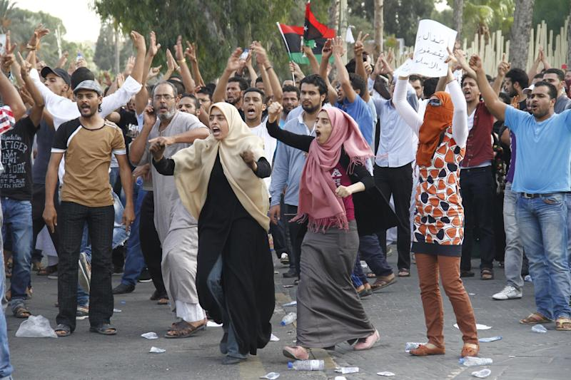Demonstrators shout their defiance after militiamen acting as police fire in the air in an attempt to disperse their protest in front of Libya's parliament. A few hundred protesters from the Libyan town of Bani Walid rallied in front of parliament in Tripoli against the weeks of siege of their hometown before soldiers fired heavy machine guns in the air to disperse the crowd. (AP Photo/Paul Schemm)