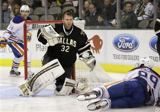 Dallas Stars' Kari Lehtonen (32), of Finland, gets to his knees after having his helmet knocked off in a collision with Edmonton Oilers' Sam Gagner (89) as Oilers' Jordan Eberle (14) watches in the second period of an NHL hockey game on Thursday, Feb. 28, 2013, in Dallas. (AP Photo/Tony Gutierrez)