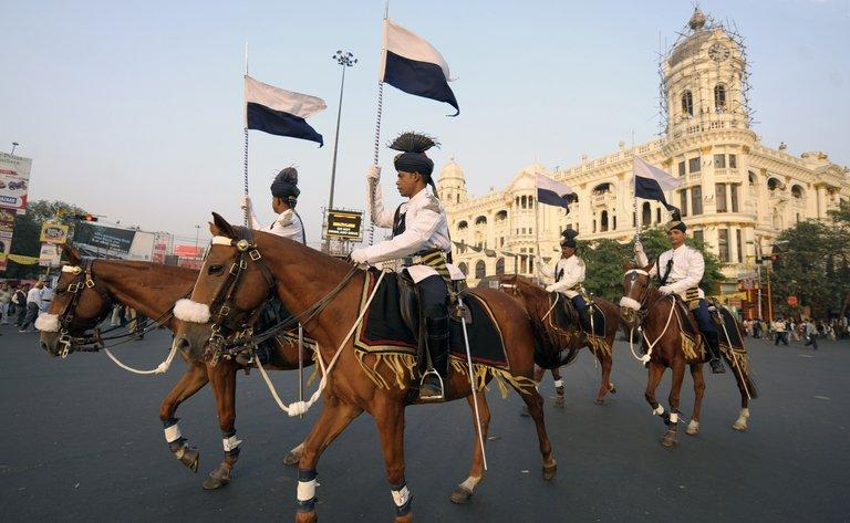 Mounted policemen ride down a street in Kolkata on December 20, 2010