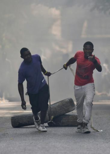 Protesters move tires to barricade a street in the Port-au-Prince suburb of Petion-Ville to protest an increase in fuel prices, which the government later suspended