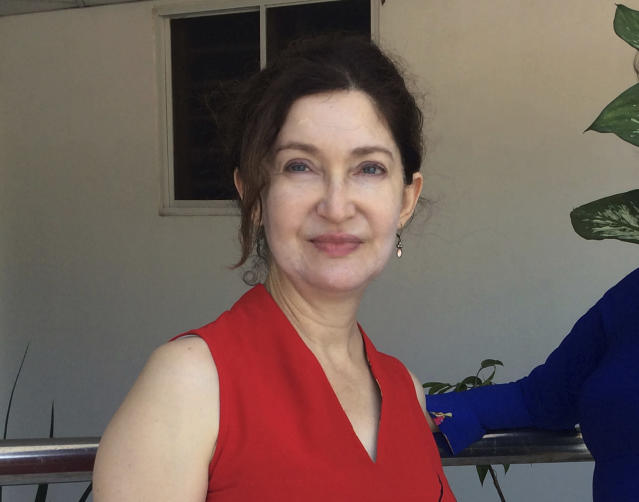 In this October 2018 photo provided by Cheryl Inzunza Blum, of Tucson, Ariz., the immigration lawyer on contract with the federal government poses for a photo in Vung Tau, Vietnam. Blum said she hasn't been paid for weeks even though she is still working, so she is turning to Airbnb as a source of income during the partial government shutdown. (John Martin Smith/Courtesy of Blum via AP)