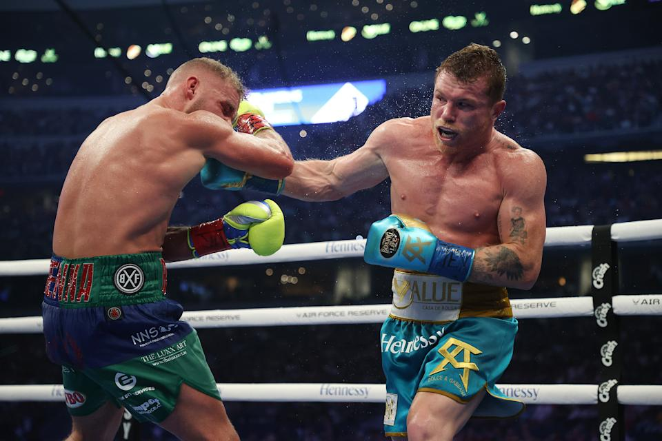 ARLINGTON, TEXAS - MAY 08:  Canelo Alvarez punches Billy Joe Saunders during their fight for Alvarez's WBC and WBA super middleweight titles and Saunders' WBO super middleweight title at AT&T Stadium on May 08, 2021 in Arlington, Texas. (Photo by Al Bello/Getty Images)