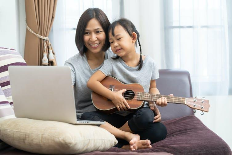 Image of a mother and daughter using laptop studying to play ukulele at home.