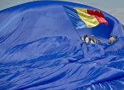 Romanians struggle to control a huge national flag during a gust of wind on the Clinceni Airfield, south of Bucharest, Romania, Monday, May 27, 2013. Romania entered the Guinness Book of records after it unveiled the largest flag ever made. It took about 200 people several hours Monday to unfurl a five-ton flag of Romania which organizers said measured 349.4 meters by 226.9 meters, about three times the size of a football pitch.(AP Photo/Vadim Ghirda)