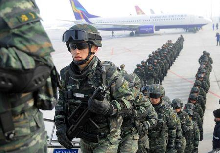 Paramilitary policemen board a plane as they head for an anti-terrorism oath-taking rally in Kashgar, from Urumqi