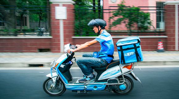 An Ele.me employee rides a motorbike while out to deliver food to a customer.