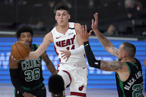 Miami Heat's Tyler Herro (14) goes up to make a pass between Boston Celtics' Marcus Smart (36) and Daniel Theis, right, during the first half of an NBA conference final playoff basketball game, Tuesday, Sept. 15, 2020, in Lake Buena Vista, Fla. (AP Photo/Mark J. Terrill)