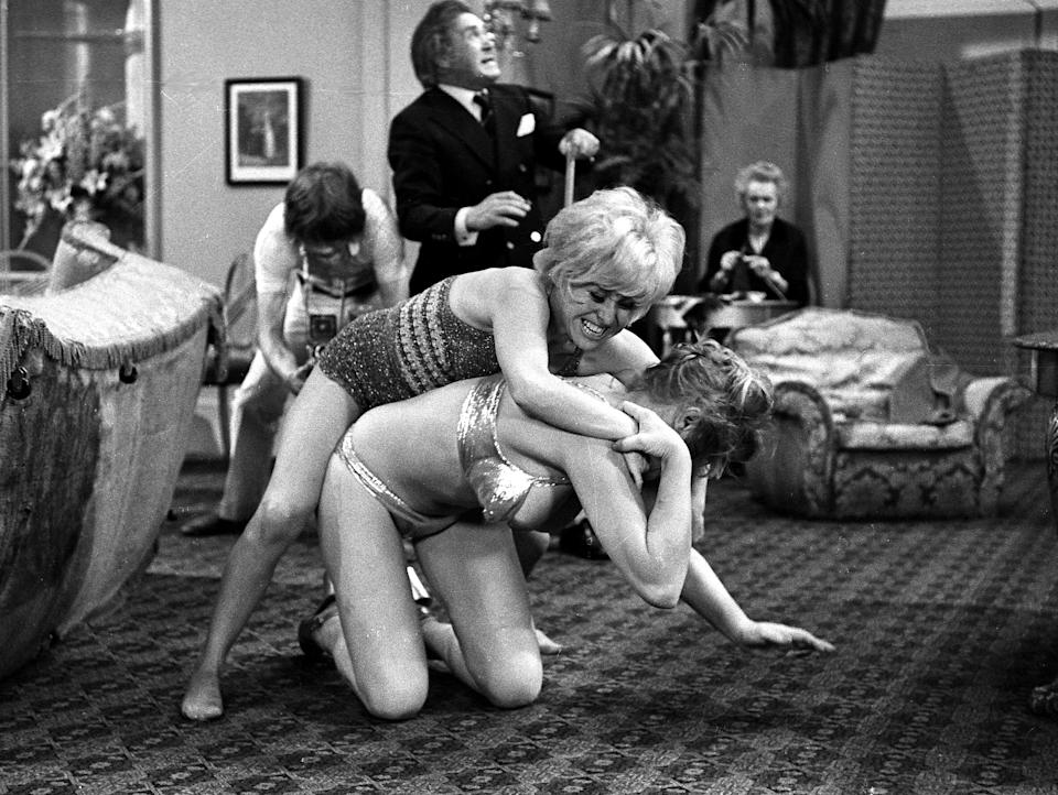 English actors Peter Butterworth and Robin Askwith watch feuding actresses Margaret Nolan and Barbara Windsor in the film 'Carry On Girls', 1973. (Photo by Larry Ellis Collection/Getty Images)