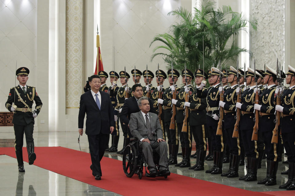 """FILE - In this Dec. 12, 2018 file photo, Ecuador's President Lenin Moreno, right, and Chinese President Xi Jinping review an honor guard during a welcome ceremony at the Great Hall of the People in Beijing, China. In 2020, Ecuador negotiated to delay for a year nearly $900 million in debt payments serviced by oil shipments, and in 2021 the U.S. International Development Finance Corporation signed an agreement with Ecuador to finance up to $2.8 billion in infrastructure projects, money that it said could be used to """"refinance predatory Chinese debt."""" (AP Photo/Andy Wong, File)"""