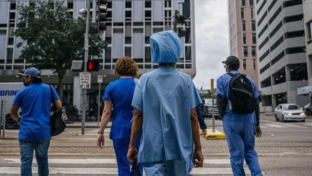 PHOTO: Medical workers and pedestrians cross an intersection outside of the Houston Methodist Hospital on June 09, 2021, in Houston. (Brandon Bell/Getty Images)