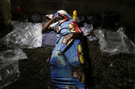 A person lies on the ground before dawn, waiting for his group to be ready to leave on foot from San Pedro Sula, Honduras, Tuesday, March 30, 2021. The group of migrants aims to reach the U.S. (AP Photo/Delmer Martinez)