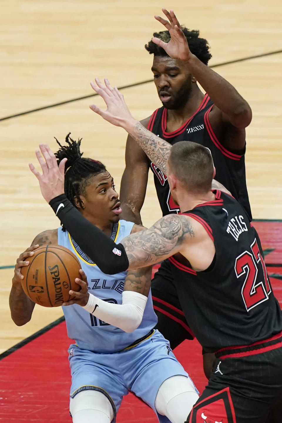 Memphis Grizzlies guard Ja Morant, left, looks to pass the ball as Chicago Bulls center Daniel Theis, right, and forward Patrick Williams defend during the first half of an NBA basketball game in Chicago, Friday, April 16, 2021. (AP Photo/Nam Y. Huh)