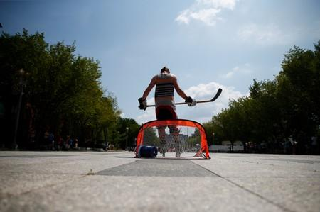 A player in a weekly pick up hockey game stands in front of the net along Pennsylvania Avenue near the White House during a heat wave in Washington