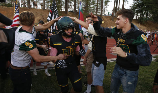 FILE - In this Aug. 23, 2019 file photo, Paradise tight end Jacob Duncan runs through a tunnel of former players during the opening ceremony of their high school football game against Williams, in Paradise, Calif. Paradise, the Northern California high school football team is preparing to play for a championship one year after most of the players and coaches lost their homes to a wildfire that nearly destroyed their town. Paradise High School will face Sutter Union High School on Saturday, Nov. 30 for the Northern Section Division III championship.(AP Photo/Rich Pedroncelli, File)