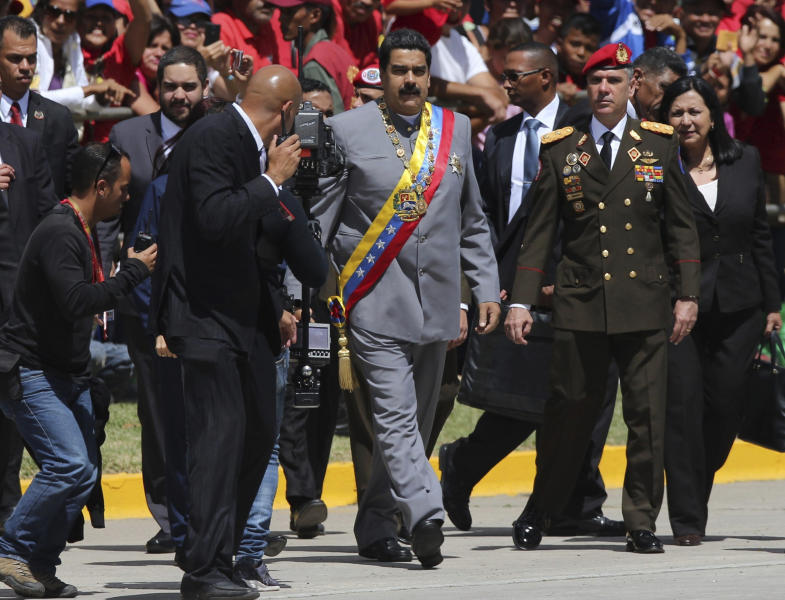 FILE - In this Feb. 1, 2017, file photo, Gen. Ivan Hernández, head of both the presidential guard and military counterintelligence, right, keeps an eye on Venezuela's President Nicolas Maduro as he arrives for a military parade at Fort Tiuna in Caracas, Venezuela. The Associated Press has learned that at least twice since 2016, the U.S. government missed chances to cultivate relations with regime insiders, including Hernández, who National Security Adviser John Bolton said backed out of a plan to topple Maduro. (AP Photo/Fernando Llano, File)