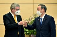 Japan's Prime Minister Yoshihide Suga greets International Olympic Committee (IOC) president Thomas Bach during their meeting in Tokyo