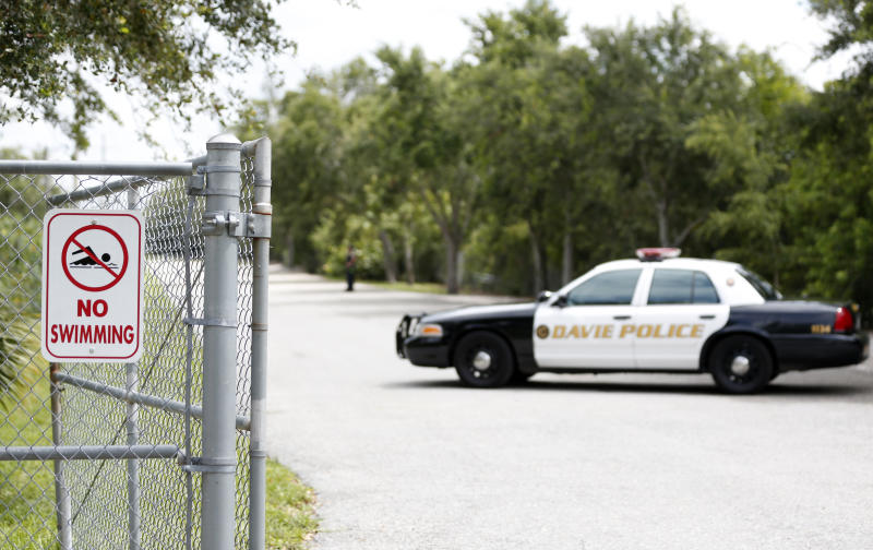 Police block the entrance to Silver Lakes Rotary Nature Park, Friday, June 8, 2018, in Davie, Fla. Someone called police after seeing a woman who was walking her dog in the park being dragged into a lake by an alligator. (AP Photo/Wilfredo Lee)