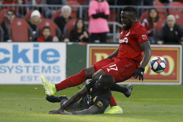 Toronto FC forward Jozy Altidore (17) and Columbus Crew defender Jonathan Mensah (4) collide during the second half of an MLS soccer match in Toronto, Sunday, Oct. 6, 2019. (Cole Burston/The Canadian Press via AP)