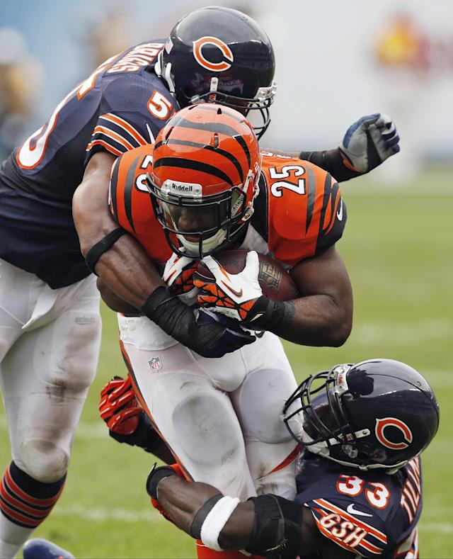 Cincinnati Bengals running back Giovani Bernard (25) is tackled by Chicago Bears cornerback Charles Tillman (33) and linebacker Lance Briggs (55) during the second half of an NFL football game, Sunday, Sept. 8, 2013, in Chicago. (AP Photo/Charles Rex Arbogast)