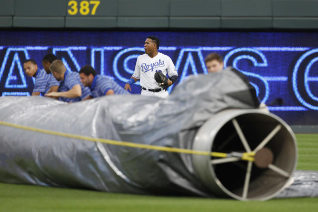 Kansas City Royals catcher Salvador Perez stands nearby as the grounds crew unrolls the infield tarp as a storm approaches before the Royals' baseball game against the Toronto Blue Jays at Kauffman Stadium in Kansas City, Mo., Thursday, Aug. 16, 2018. (AP Photo/Colin E. Braley)
