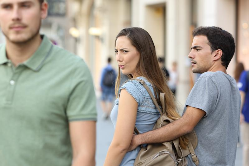 Disloyal woman looking at another man and her upset boyfriend.
