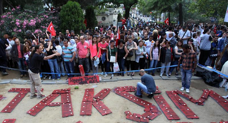 In this Sunday, June 2, 2013 photo protesters of different ages watch artists make with red painted wooden pieces the words ''Taksim'' during a protest at the Taksim square in Istanbul. Prime Minister Recep Tayyip Erdogan has enjoyed popularity the likes of which has been unseen in Turkey in decades. The divide between the country's staunchly secular, mostly urban voters who tend to oppose Erdogan, and his traditional support base of the religious, largely rural population remain, the latest protests have begun to blur the line between the two. (AP Photo/Thanassis Stavrakis)