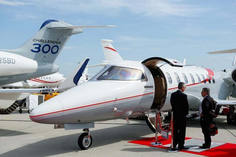 Visitors talk in front of a Bombardier Challenger aircraft in the static display area during the EBACE in Geneva