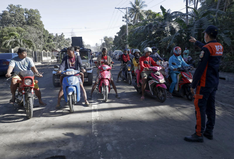 A fireman talks to motorcycle riders at the gates as authorities enforced total evacuation of residents living near Taal volcano in Agoncillo town, Batangas province, southern Philippines on Thursday Jan. 16, 2020. Taal volcano belched smaller plumes of ash Thursday but shuddered continuously with earthquakes and cracked roads in nearby towns, which were blockaded by police due to fears of a bigger eruption. (AP Photo/Aaron Favila)