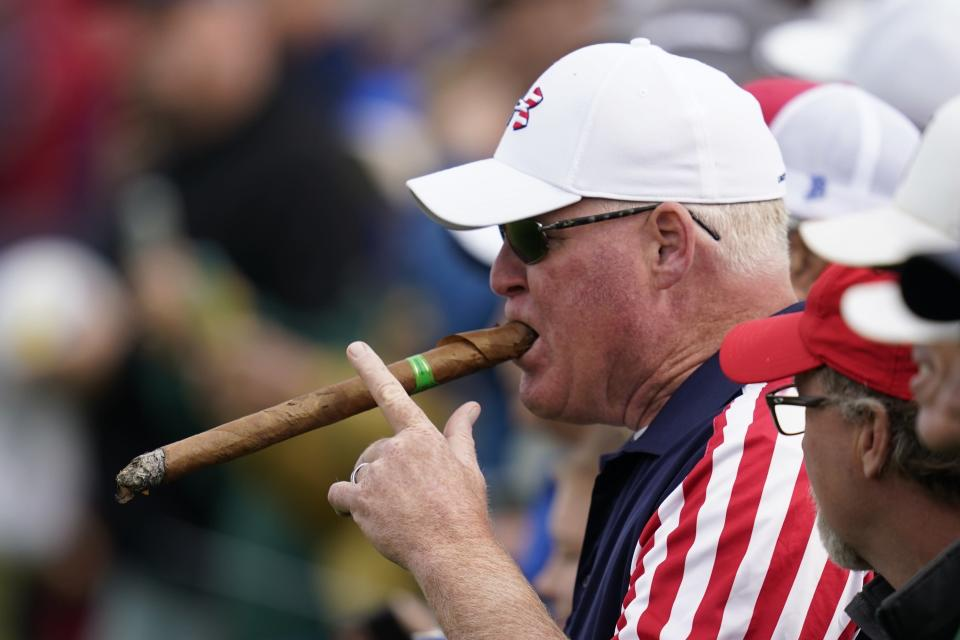 A fan smokes a large cigar on the 10th hole during a practice day at the Ryder Cup at the Whistling Straits Golf Course Wednesday, Sept. 22, 2021, in Sheboygan, Wis. (AP Photo/Ashley Landis)