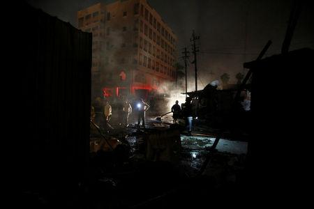 Members of the Iraqi security forces inspect the site of a suicide car bomb attack in Baghdad, Iraq