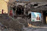 Campaign posters for parliamentary elections are displayed near destroyed buildings from fighting between Iraqi forces and the Islamic State group in Mosul, Iraq, Sunday, Oct. 3, 2021. Iraq on Sunday, Oct. 10, holds its fifth election since the 2003 U.S.-led invasion that toppled Iraqi dictator Saddam Hussein, with most Iraqis longing for real change. (AP Photo)