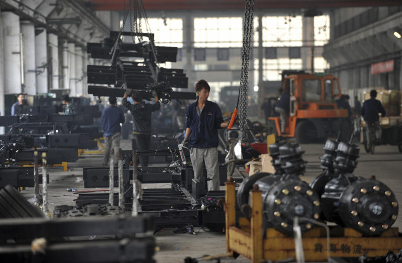In this photo taken Saturday Oct. 20, 2012, a worker prepares to hoist metal parts at the assembly line at a bus manufacturer in Dandong city in northeast China's Liaoning province. China's manufacturing improved this month, adding to signs an economic recovery might be taking shape after a sharp slump in the world's No. 2 economy. (AP Photo) CHINA OUT